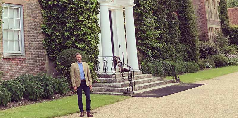 John-Paul McGarry standing in front of a country home.