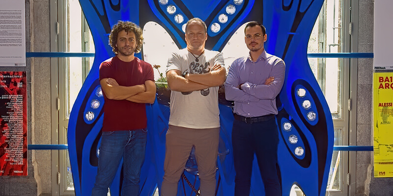 Three men, with crossed arms, standing in front of a blue, elaborate, guitar-shaped installation