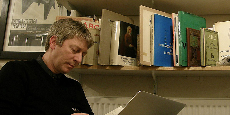 Dr Mike Harkins sitting next to shelf of books and reading