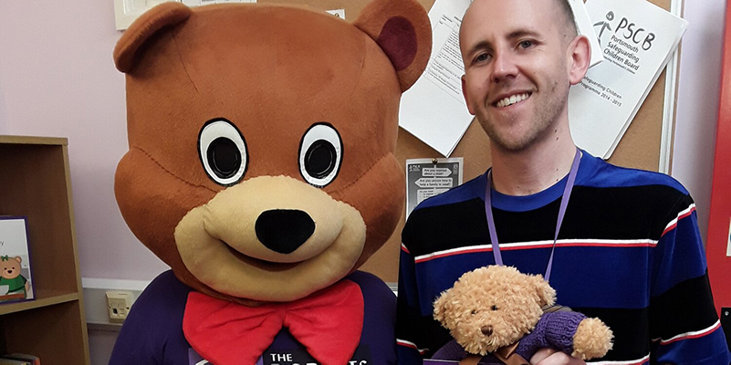 Nathan Beattie smiling next to bear mascot at the Roberts Centre