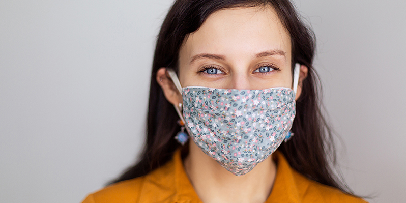 Woman with blue eyes wears a patterned handmade mask over her nose and mouth