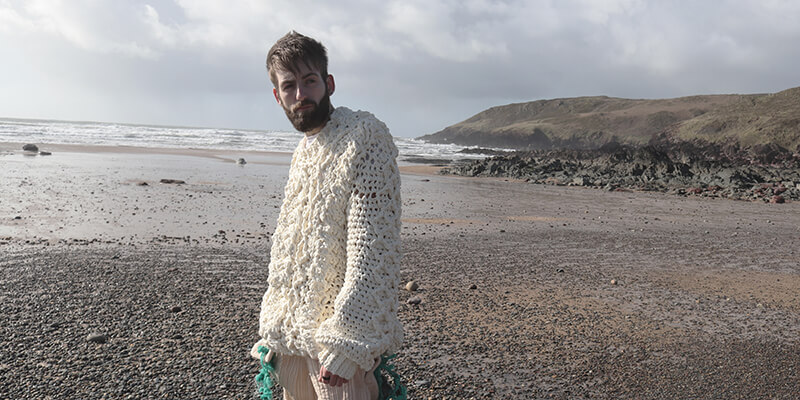 A person with beard, wearing a thick woolly jumper, staring out on the beach