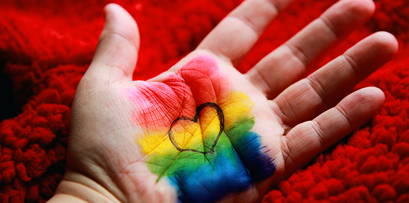 A palm decorated with rainbow paint and an outline of a heart