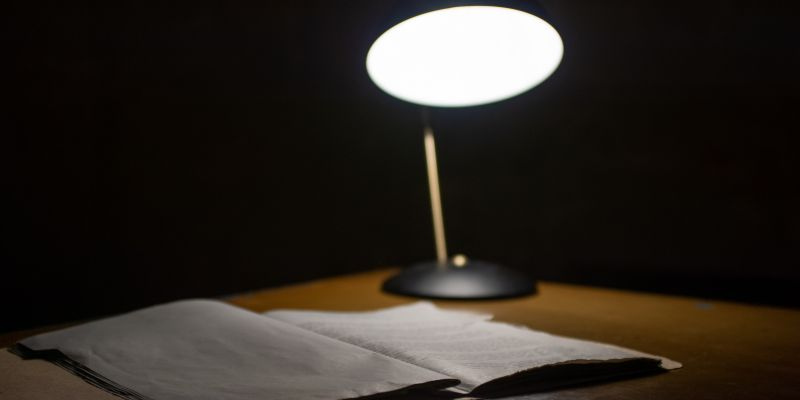 Casefile on desk, illuminated by a lamp