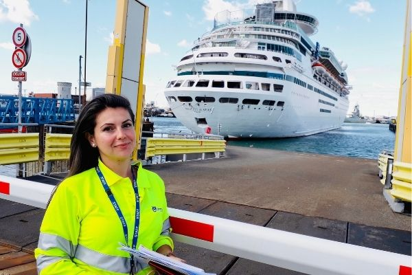 Female alumni stood in a high vis coat in front of a ferry at the Port