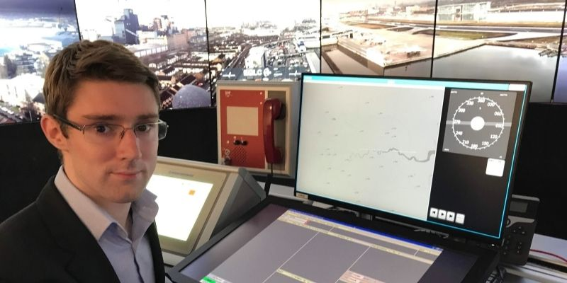 Alumnus sat at a air traffic control station desk looking at the camera