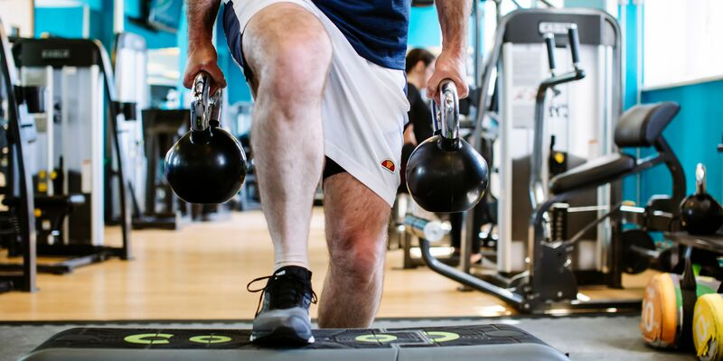 Man holding weights uses step block in gym
