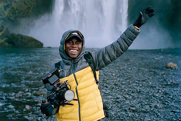 A man in a padded hooded jacket, smiling and waving, with a camera in hand against a waterfall in the background
