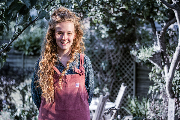 A female person in a wild garden, dressed in dusty pink dungarees, smiling to camera
