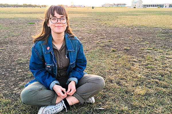 A female person with glasses, wearing denim jacket and khaki jumpsuit, sitting cross-legged on a grass field, smiling to camera