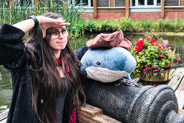 A female person with glasses, wearing a black jacket and red overshirt over a black top, saluting to her left near a plush whale atop a mini-cannon