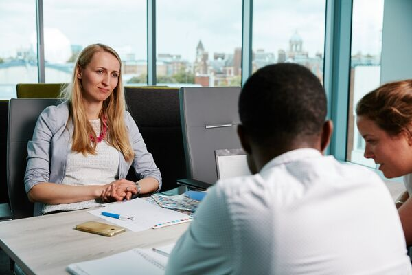 Female professional in meeting looks at colleagues deliberating