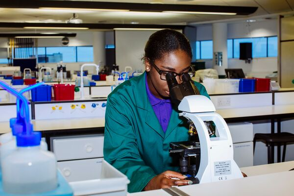 A female student in the lab looking through a microscope