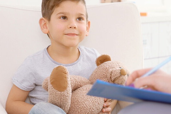 A young boy sat on a sofa with a teddy in a doctors room