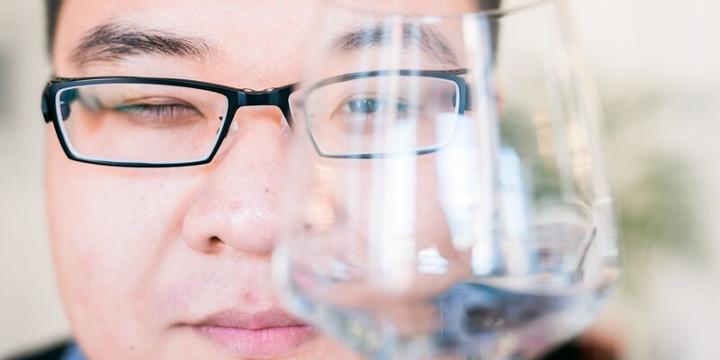 Male student looking through a clear wine glass