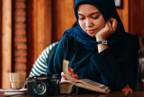 a-young-woman-in-a-head-scarf-sitting-at-a-table-reading-a-book