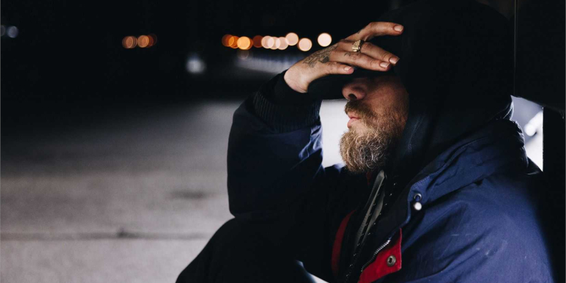 Man with beard sat at roadside covering his face