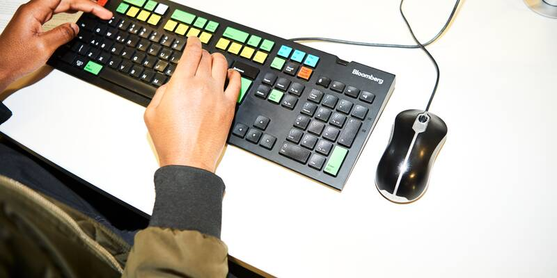 Person in coat using colourful media keyboard
