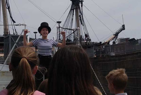 Performers on boat with female lead in top hat and striped shirt