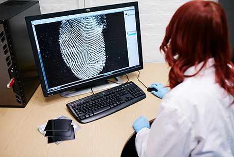 Woman in lab coat and blue gloves examining finger print on computer screen
