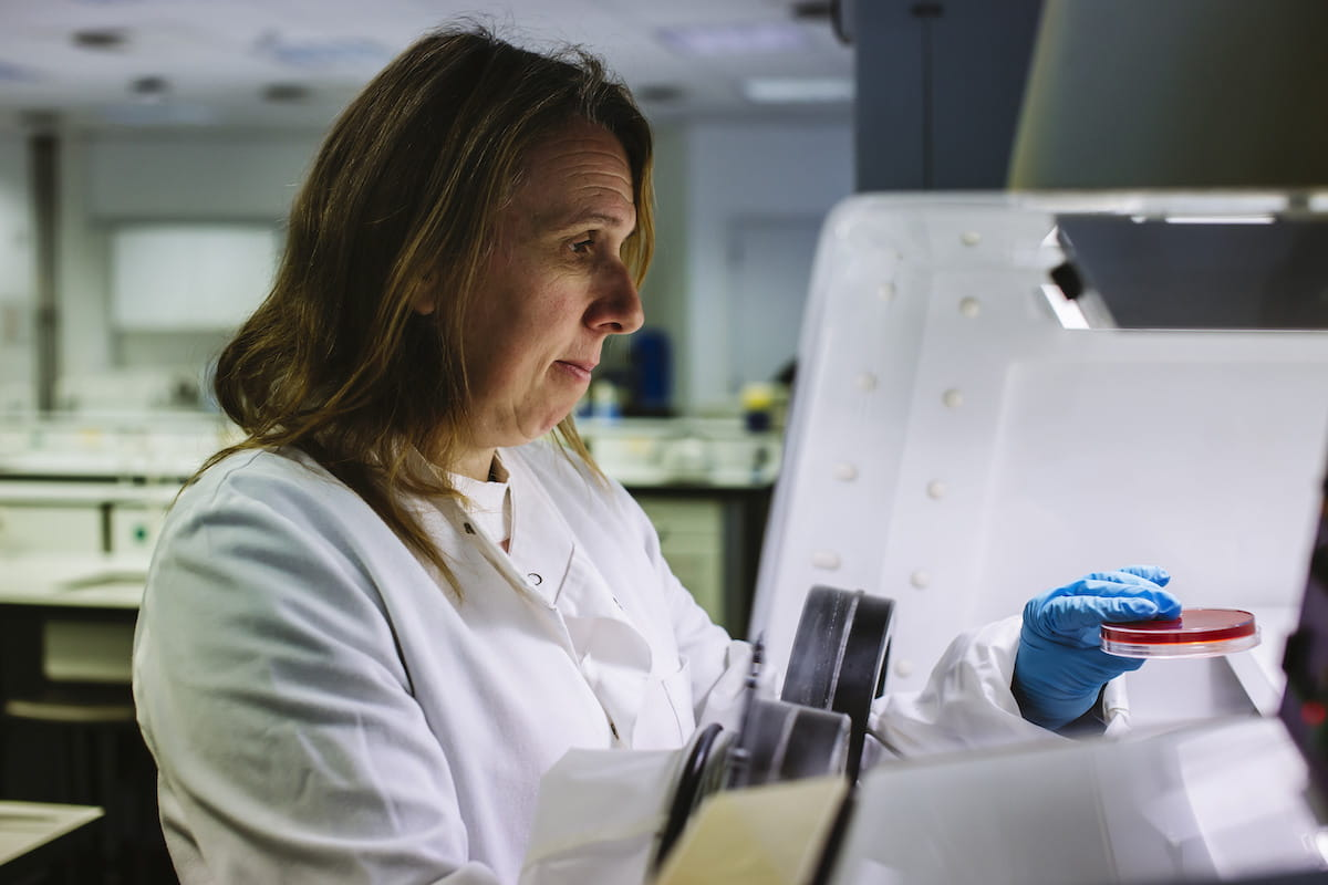 Dr Sarah Fouch wearing a white lab coat working with samples in a lab