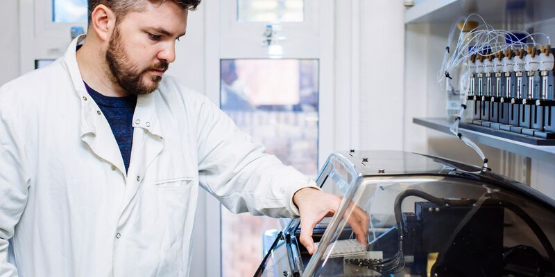 Male scientist in lab coat working with samples