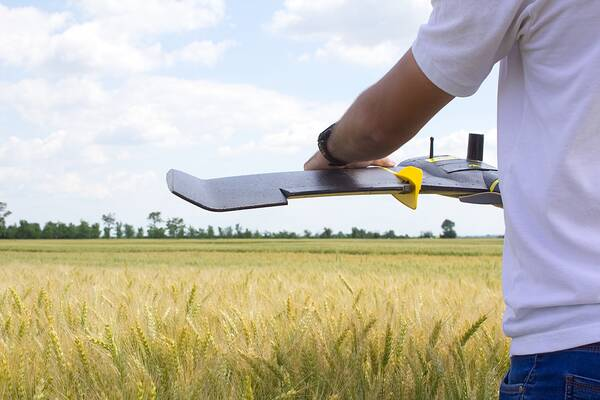 Man holding drone in a field