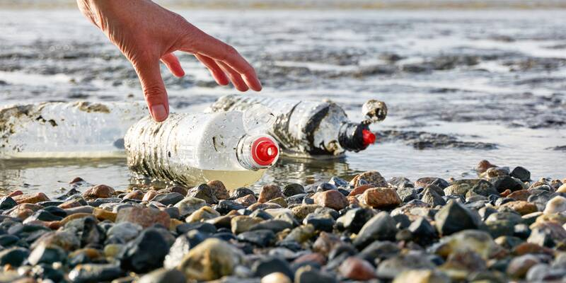Hand picking up plastic bottle on a beach