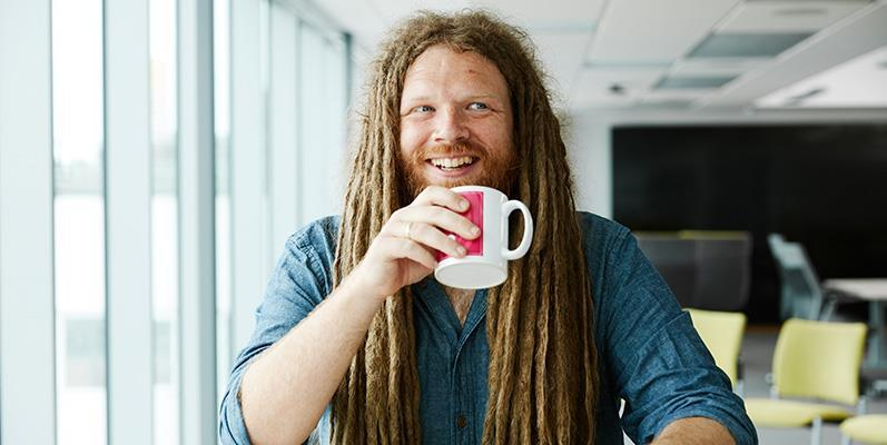 Mathematician Dr Jamie Foster holding a cup of coffee