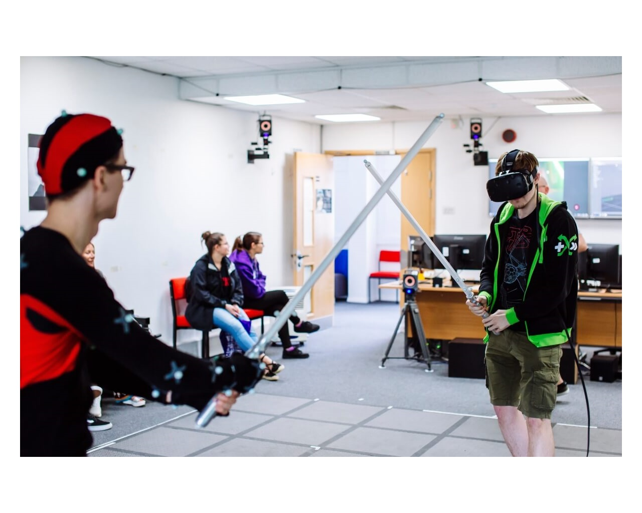Two students using light sabres in virtual reality lab