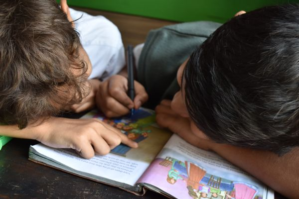 Two boys reading and writing in a book.