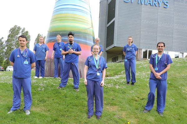 Group of nursing students wearing blue scrubs standing on grass.