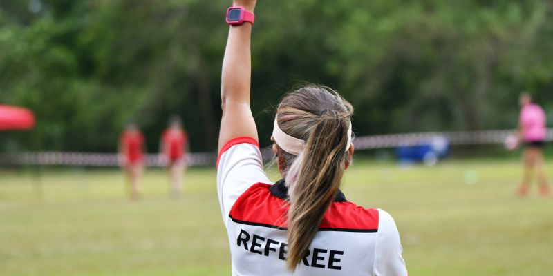 Back view of female referee holding up a card