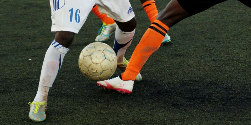 Image of two people's legs as they play football