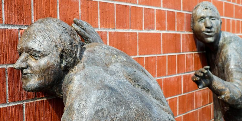 Sculptures of two people with ears pressed against a brick wall