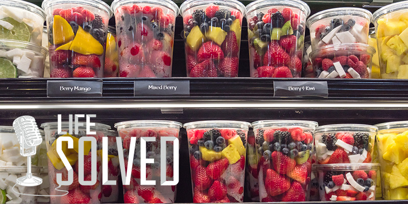 Plastic packaged fruit in yellow and red on shop shelves