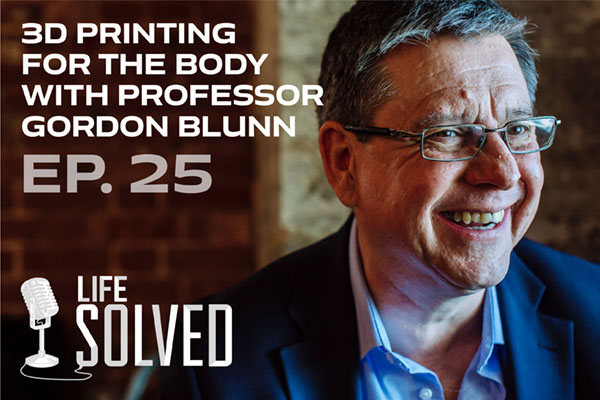 Professor Gordon Blunn wearing suit and smiling. Life Solved text and logo in corner