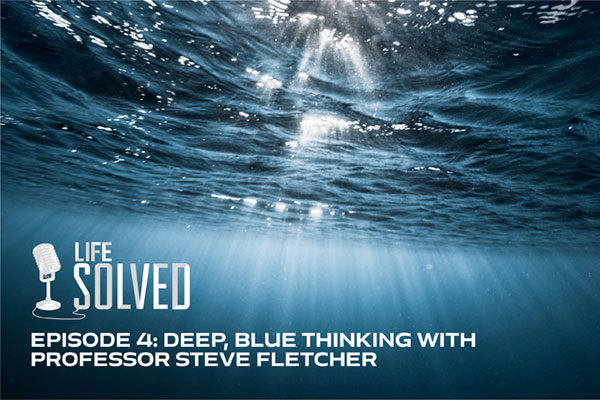 Just below the surface in the ocean, dark blue, light streaming through. Life Solved logo and title.