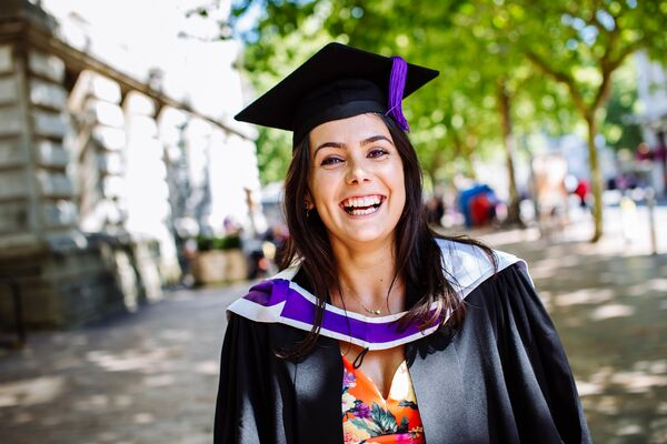 Graduate and PhD student Sorina smiling in graduation gown