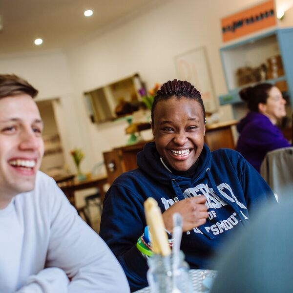 Students smiling and socialising in a cafe