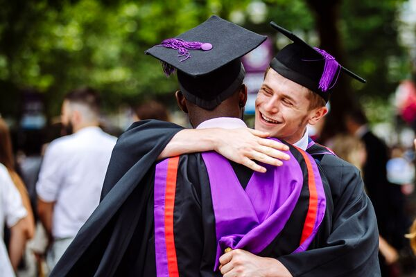 Two male students in graduation gowns hugging